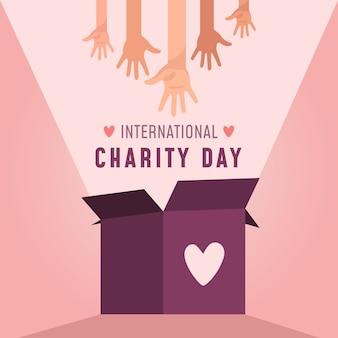 O dia internacional da caridade em mãos e caixa de doações