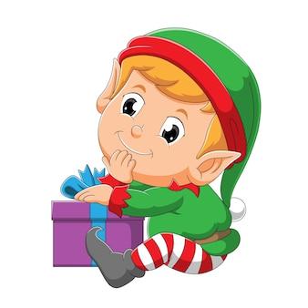 O elfo com a cara feliz está sentado perto da caixa de presente da ilustração