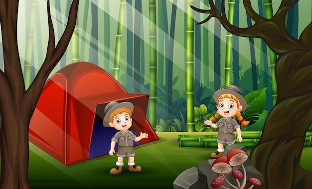 O explorador, menino e menina, acampando na floresta de bambu