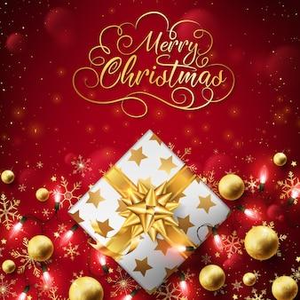 O fim acima da caixa dourada do natal veste acima o fundo com luzes da corda.