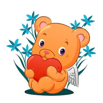 O fofo urso cupido está sentado e segurando o coração colorido no jardim cheio de flores de ilustração