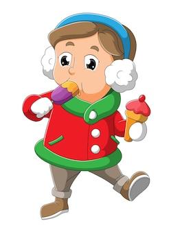 O garotinho com a fantasia de inverno está comendo a pilha de gelo da ilustração
