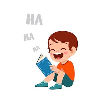O garotinho cule lendo um livro engraçado e rindo tanto