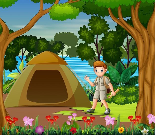 O garoto explorador acampar à beira do lago