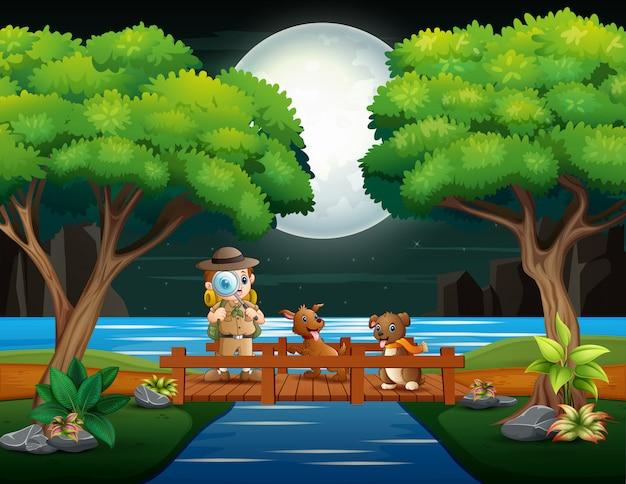 O garoto explorador com dois cães na ponte de madeira