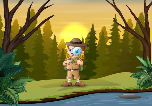 O garoto explorador com lupa na floresta