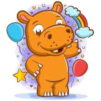 O hipopótamo em pé ao redor dos balões com a cara feliz