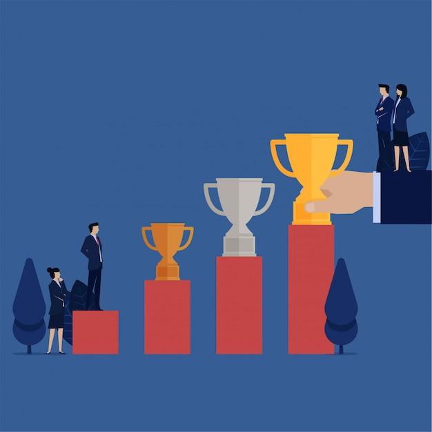 O homem de negócio vê o troféu de prata do ouro de bronze acima da metáfora da carta do crescimento da carreira.