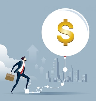 O homem de negócios mantém inflacionar um dólar da economia da bolha. conceito de investimento