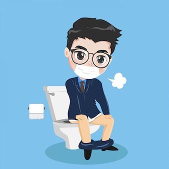 O homem de negócios novo está sentando-se no toalete.