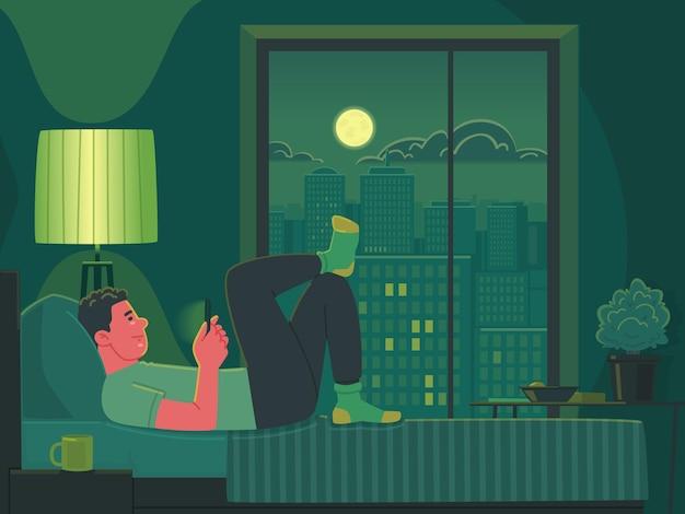 O homem deita na cama à noite e olha para o smartphone, telefone viciado em navegação na internet