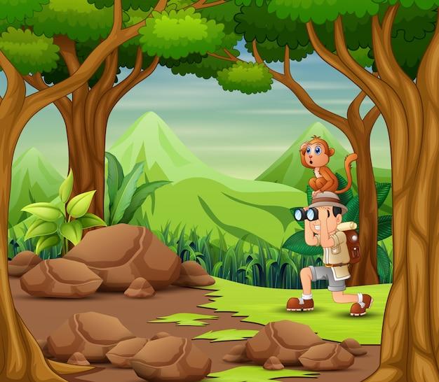O homem do explorador com o macaco na floresta