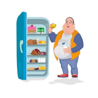 O homem gordo come um hambúrguer em uma geladeira aberta em que há muitos alimentos prejudiciais