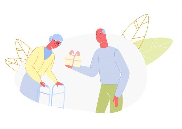 O homem idoso dá o aniversário amarelo da caixa de presente da mulher
