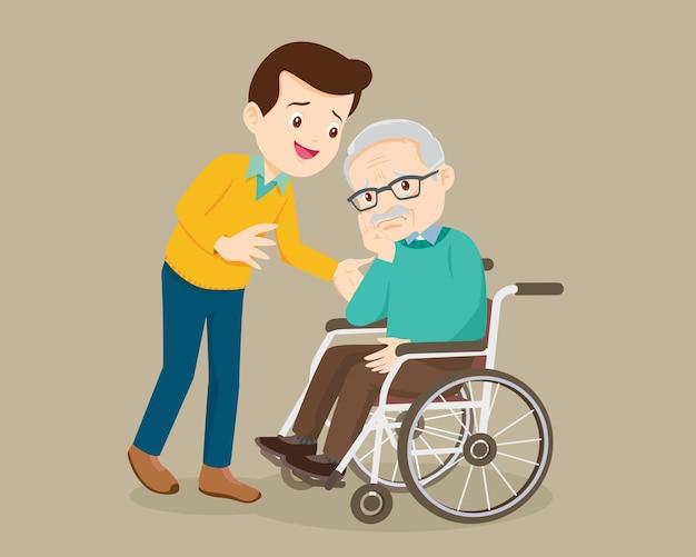O homem idoso senta-se em uma cadeira de rodas e o filho com ternura coloca as mãos em seus ombros.