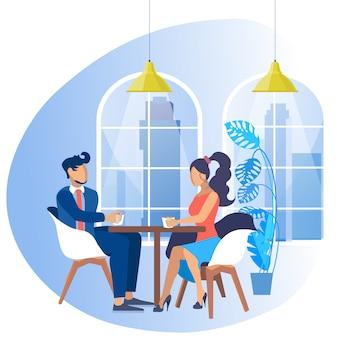 O homem no terno e na mulher de negócio com senta-se na tabela.