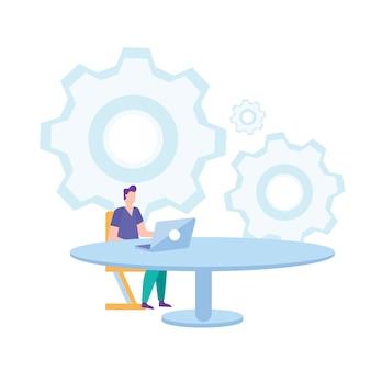 O homem senta-se na cadeira na tabela que trabalha no portátil.