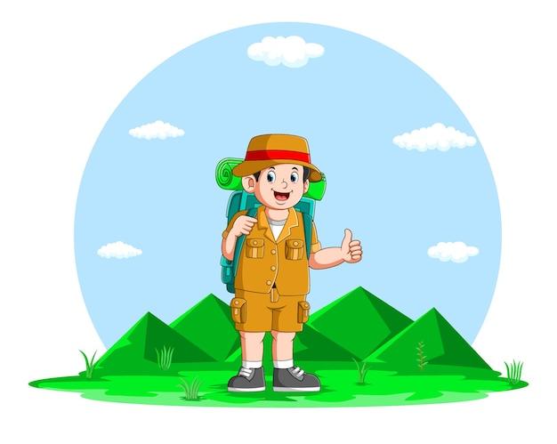 O jovem está caminhando com a mochila grande na montanha