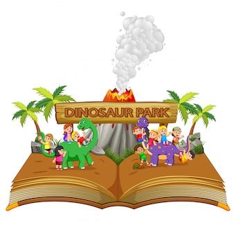 O livro de histórias com as crianças brincando com o dinossauro e o vulcão
