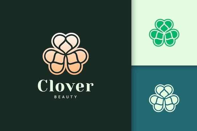 O logotipo da folha de trevo em uma cor dourada luxuosa representa sorte ou erva