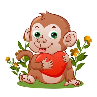 O macaco fofo com a cara feliz está sentado e segurando o grande coração de ilustração
