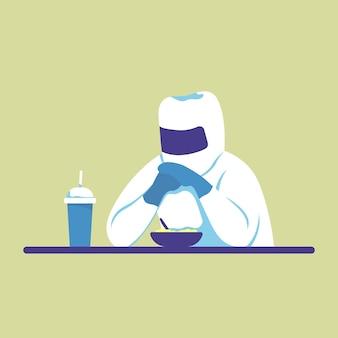 O médico de uniforme está jantando à mesa por quarentena de epidemia de coronavírus