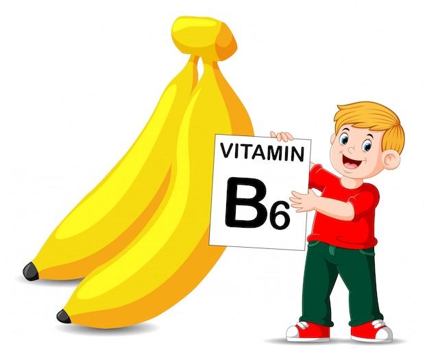 O menino ao lado da banana está segurando a placa de vitamina b6