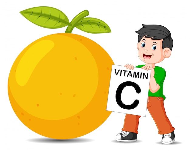 O menino ao lado da laranja está segurando a placa de vitamina c