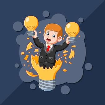 O menino com a boa ideia segurando a lâmpada amarela nas mãos