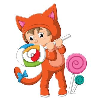 O menino com a fantasia de gato está mordendo o pirulito da ilustração