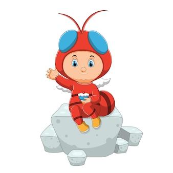 O menino com a fantasia de mosca está sentado sobre os cubos de açúcar da ilustração