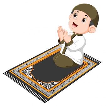 O menino com o boné marrom está rezando no tapete de oração marrom