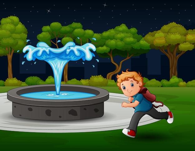 O menino da escola correndo na paisagem do parque