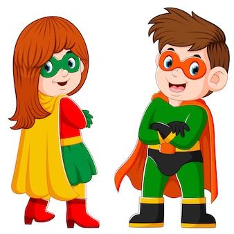 O menino e a menina está usando o traje de super-heróis e a máscara