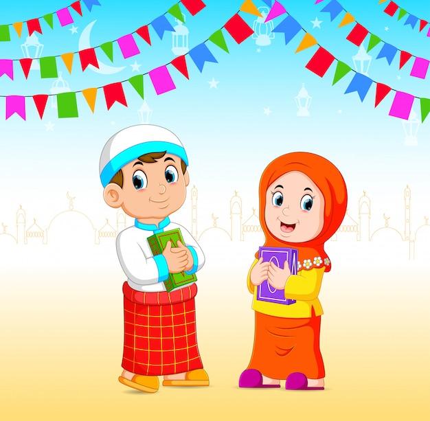 O menino e a menina estão segurando o al quran no evento do ramadã