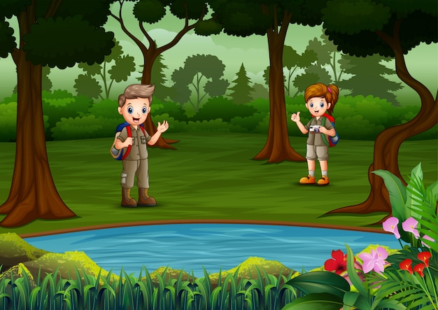 O menino e a menina exploradores descansam à beira do lago