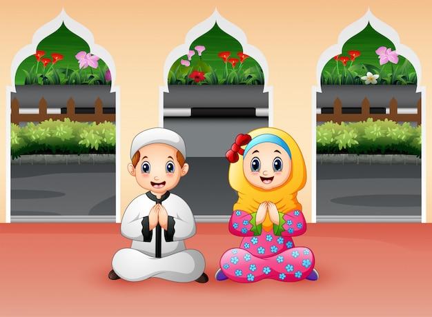 O menino e a menina muçulmanos estão rezando na mesquita