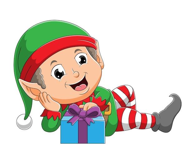 O menino elfo fofo está deitado perto da caixa de presente da ilustração