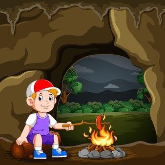 O menino está acampando e queimando a salsicha na fogueira