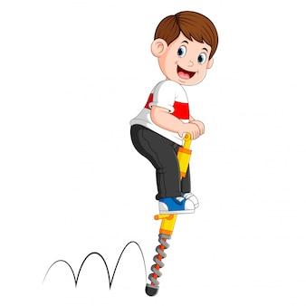O menino está brincando com o bastão de salto