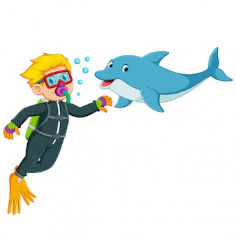 O menino está brincando com o golfinho debaixo d'água
