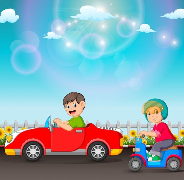 O menino está dirigindo o carro e aquele está montando a scooter