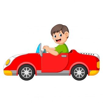 O menino está dirigindo o carro vermelho com o bom posando