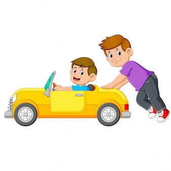 O menino está empurrando o carro amarelo com seu amigo nele