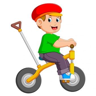 O menino está pedalando na bicicleta amarela com o suporte