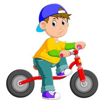 O menino está posando na bicicleta vermelha