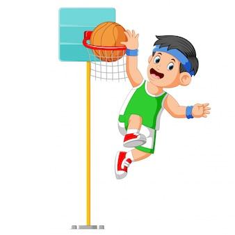 O menino está pulando para fazer o placar na cesta