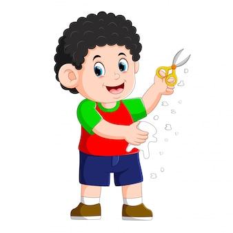 O menino está segurando a tesoura para cortar o papel