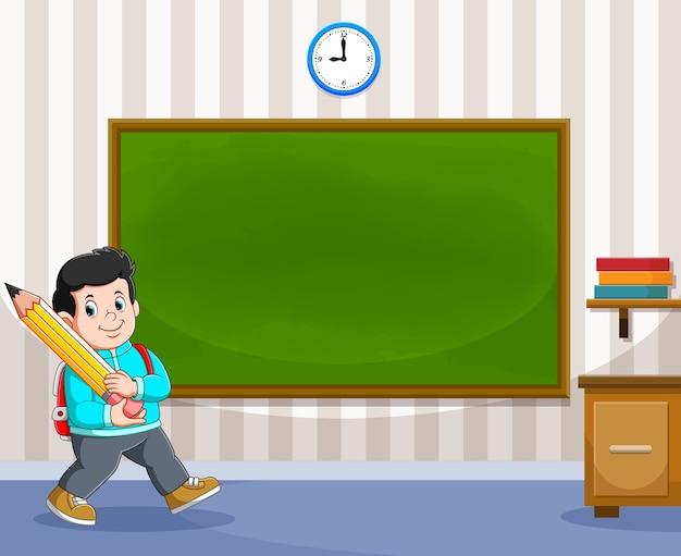 O menino está segurando o lápis grande ao lado do quadro-negro