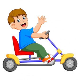 O menino está sentado e andando no triciclo